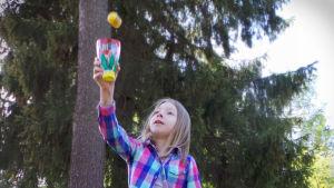 """Ruutupaitainen tyttö koettaa napata pallon kuppiin pelatessaan itse tehtyä """"pallo ja kuppi""""-peliä"""