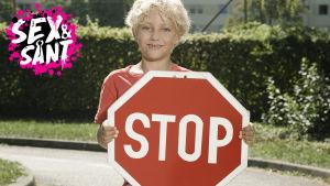 en ung pojke som står ute på gatan med en stop skyllt i handen
