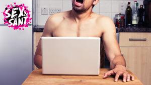 en man som sitter vid ett bor, ser på sin dator och masturberar