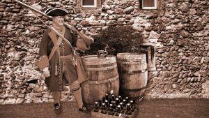 Sotilas 1800-luvun lopun asussa, olutkori vierellä.
