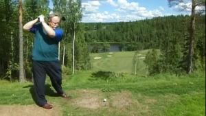 Presidentti Ahtisaari valmiina pitkään lyöntiin golfkentällä.