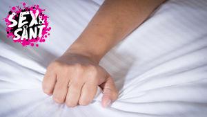 en hand som skrynklar lakanen i en säng
