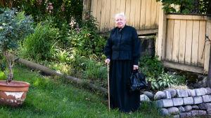 En äldre kvinna i grått hår och svart klänning. Det är Anne Ingman som föreställer konstnären Helene Schjerfbeck.