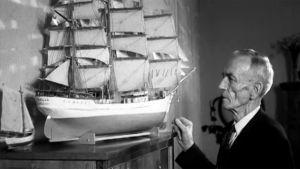 Ikääntynyt merikapteeni tarkastelee haikeana purjelaivan pienoismallia.