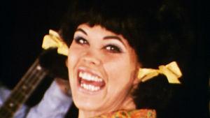 Ann-Christine Nyström laulaa yhtyeen säestämänä E-liikkeen mainosfilmissä.