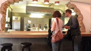 Besökare förser sig med mat vid disken.