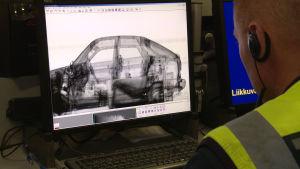 Tullens tjänsteman kontrollerar ett fordon som genomlysts med tullens apparatur.