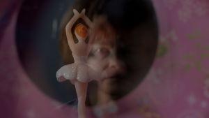 Kuva peilistä, josta heijastuu Eijan kasvot ja balleriinasoittorasia