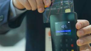 Pankkikortin etälukija lähietäisyydellä, käsi pitelee korttia sekä päätettä