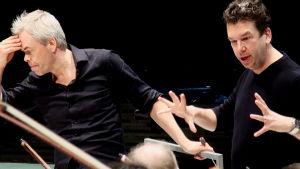 Dirigent Hannu Lintu och Sebastian Fagerlund under övning med orkester.