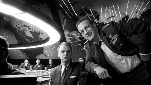 Kenraali Buck Turgidson (George C. Scott, oikealla) tuumii. Kuva elokuvasta Tohtori Outolempi