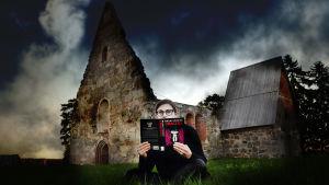 Kaisa Pulakka istuu rauniokirkon edessä lukien Draculaa