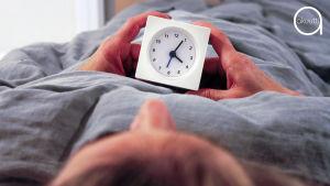 Nainen makaa sängyssä herätyskello kädessään.