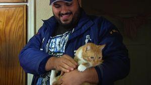 Musa Al-Shirefi med katten Zaza i famnen.