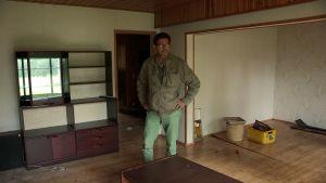 Mies tutkailee tyhjää vanhaa taloa