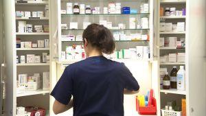 sairaanhoitaja jakaa potilaiden lääkkeitä sairaalan lääkekaapilla.