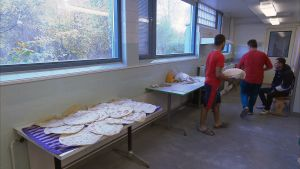 MIkkelin vastaanottokeskuksessa miehet leipovat perinteistä arabialaista leipää.