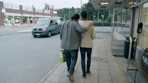 Peter och Ahmed går bortåt, Peter har sin arm över Ahmeds axel