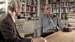 Christoffer Strandberg utklädd till Jörn Donner. Han är sminkad för att se gammal ut samt har stora ögonbryn. Han har också på sig en säckig kavaj. Han sitter och pratar med Jörn i Jörns arbetsrum. I bakgrunden syns bokhyllor fyllda med böcker.