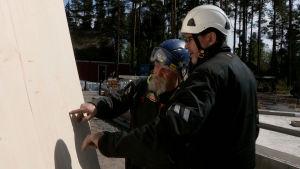 Miehet tutkivat elementin laatua rakennustyömaalla