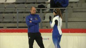 Janne Hänninen och Elina Risku diskuterar på isen i Inzell.