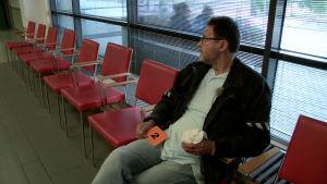 Mies odottaa lääkärin vastaanotolla sormi paketissa