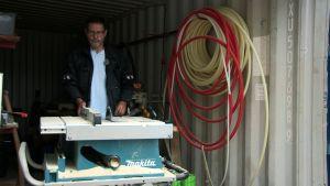 Mies käynnistelee sirkkeliä rakennustyömaalla