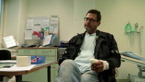 Mies istuu lääkärin vastaanotolla sormi paketissa