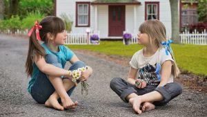 Kuvituskuva kuunnelmaan Onnelin ja Annelin talo, kaksi pikkutyttöä puutalon edessä.