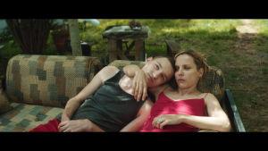 Wojtek (Stanislaw Cywka) och hans mamma Agnieszka (Julia Kijowska) halvligger i en soffa på gårdplanen.