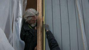 Mies mittaa ikkunan karmeja