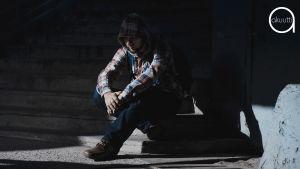 huppupäinen mies istuu varjossa portailla