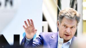 President Niinistö pratar med handen upphöjd.