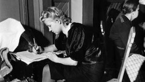 Nuori nainen kirjoittaa kirjettä matkalaukun päällä väliaikaismajoituksessa evakkomatkalla.