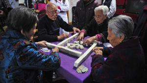 Vanhukset pelaavat mahjongia yksityisessä hoitokodissa.