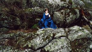 Tyttö istuu juhlavaatteissa metsässä.