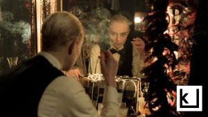 Mies katselee itseään peilistä savuke kädessään.