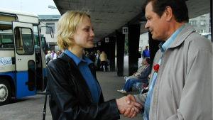 Nuori nainen ja Heikki tervehtivät linja-autoasemalla
