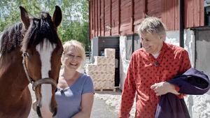 Helena Bergström leder en häst och Lars Lerin ser på.