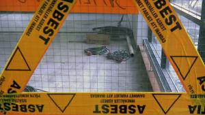 Asbestista varoittava teippi työmaan ikkunalasissa.