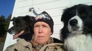 Agneta Andersson poserar tillsammans med två hundar.