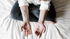Nainen istuu sängyllä kämmenet ylöspäin.