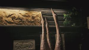 Tre svanar i trä sträcker upp sina huvuden. I bakgrunden träreliefer på mörka väggar.