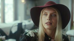 Donna (Alina Tomnikov) istuu kahvilassa viininpunainen hattu päässään.