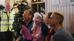 Blond, långhårig kvinna sitter på bänk i sällskap med några andra personer och viftar med en solfjäder.