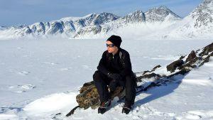 Jamie istuu kivillä. Taustalla vuoristoa.