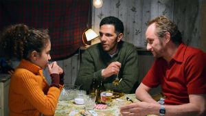 Kaksi miestä ja tyttö keskustelevat pöydän ääressä.