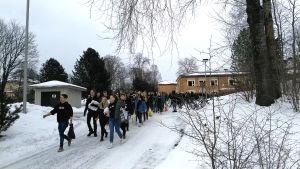 Ungdomar som går på en vintrig gata.