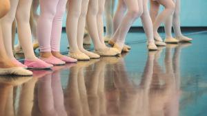 Balettitanssijalasten jalkoja rivissä.