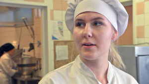 Ung kockstuderande flicka i kockmössa i utbildningskök.